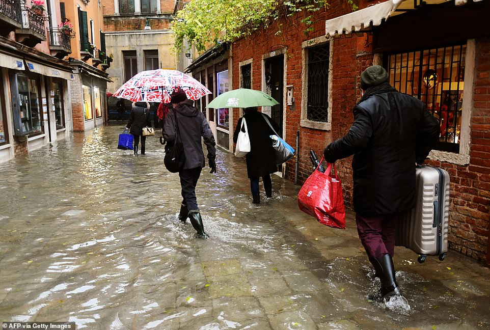 People walk across a flooded street on Tuesday in Venice. Bad weather including heavy rain and high winds caused the tide in Venice to rise and flood waters reached a height of 122cm this morning