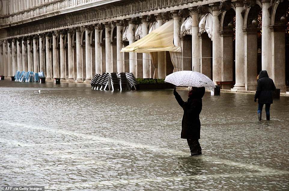 A person takes photos while standing on a flooded St. Mark's Square on December 8