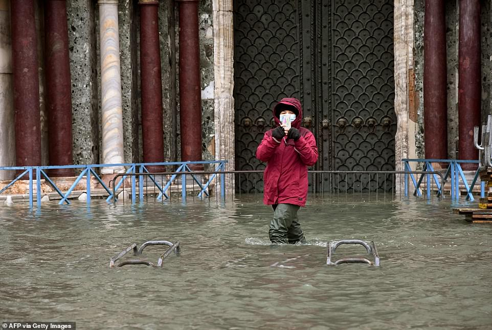 "A person takes photos while standing on a flooded St. Mark's Square on December 8, in Venice following a high tide ""Alta Acqua"" event following heavy rains and strong winds"