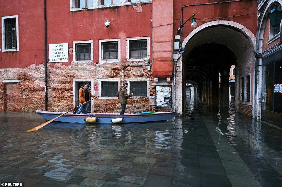 People were seen riding a traditional boat in a flooded street in Venice, Italy