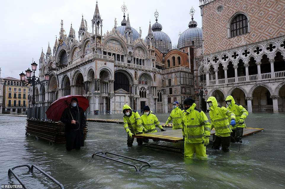 Workers are seen in the flooded St. Mark's Square during high tide