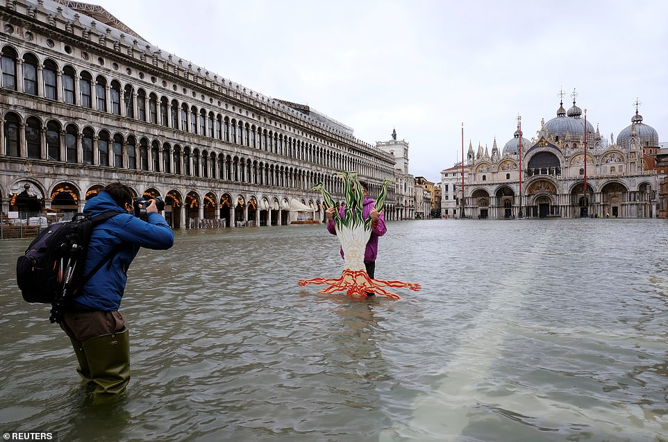 A person poses for a photo in flooded St. Mark's Square
