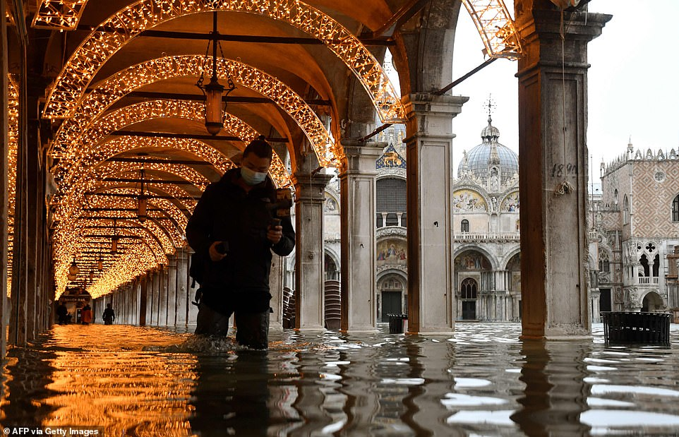 "A man walks across an arcade by a flooded St. Mark's Square on December 8, 2020 in Venice following a high tide ""Alta Acqua"" event following heavy rains and strong winds, and the mobile gates of the MOSE Experimental Electromechanical Module that protects the city of Venice from floods, were not lifted"