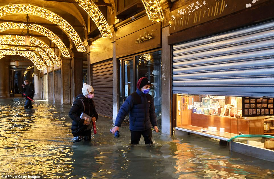 "People walk across an shopping arcade by a flooded St. Mark's Square on December 8, in Venice following a high tide ""Alta Acqua"" event following heavy rains and strong winds"