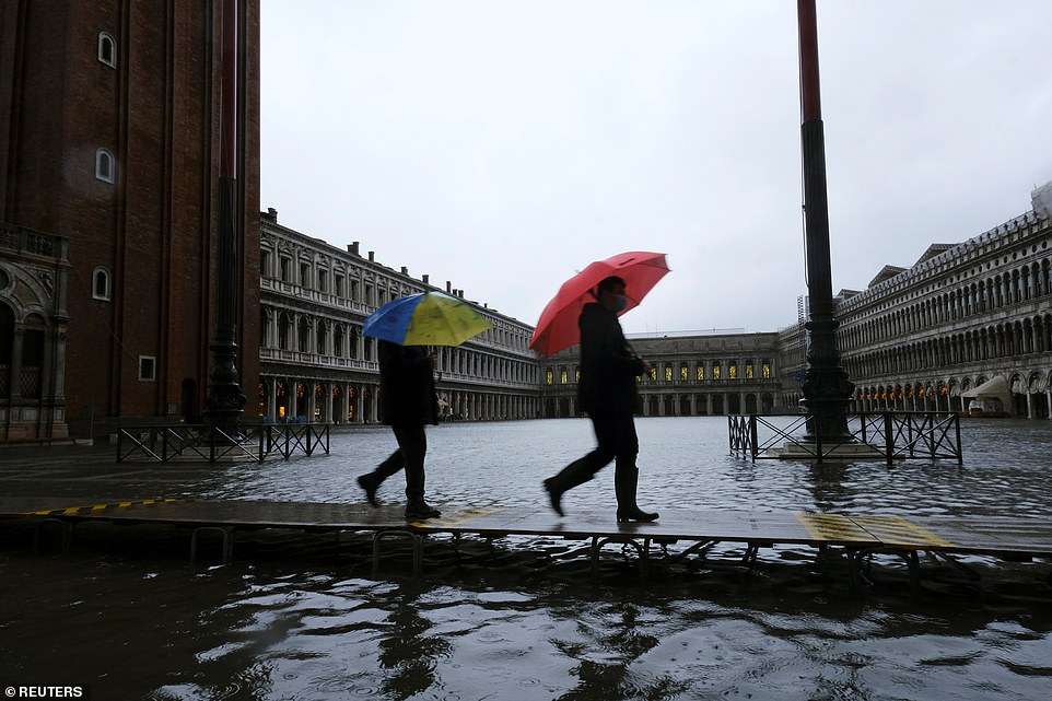 Heavy rain and high winds caused the tide in Venice to rise. Pictured two people in umbrellas walking in St. Mark's Square