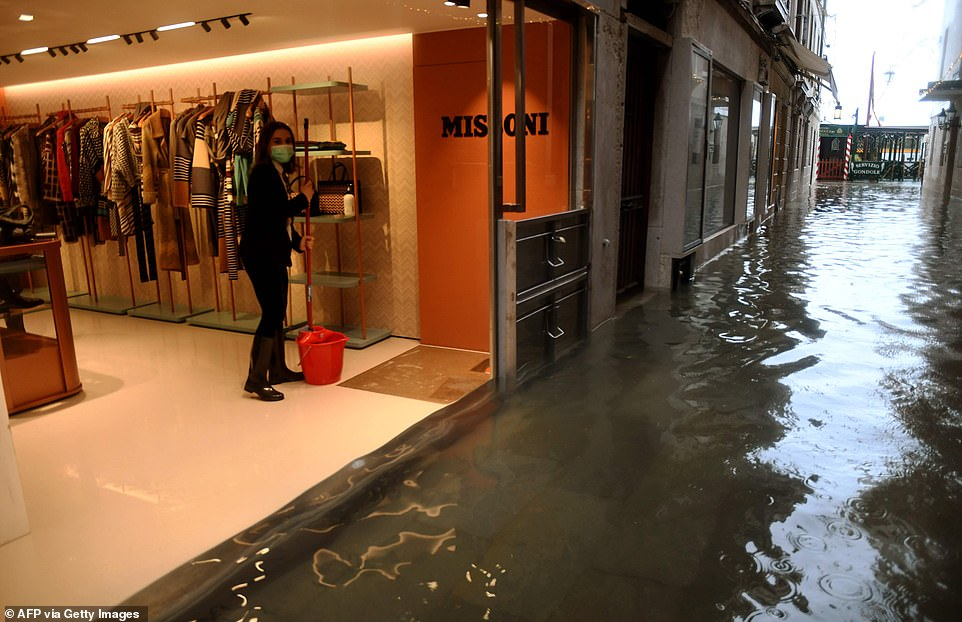 "A woman clears her flooded shop on December 8, 2020 in Venice following a high tide ""Alta Acqua"" event following heavy rains and strong winds, and the mobile gates of the MOSE Experimental Electromechanical Module that protects the city of Venice from floods, were not lifted"