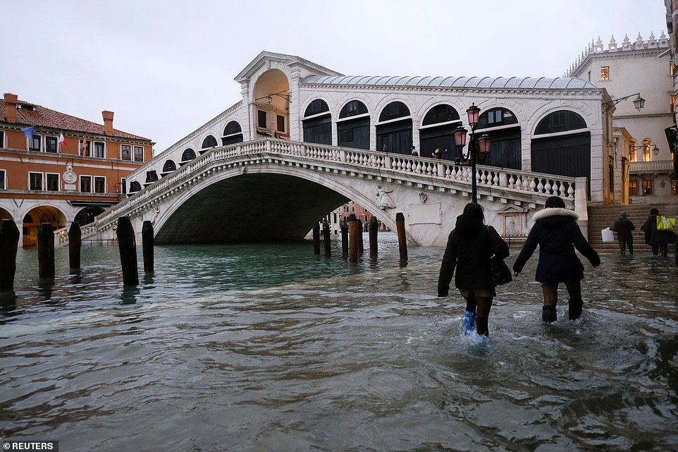 People walking past the Rialto Bridge during high tide