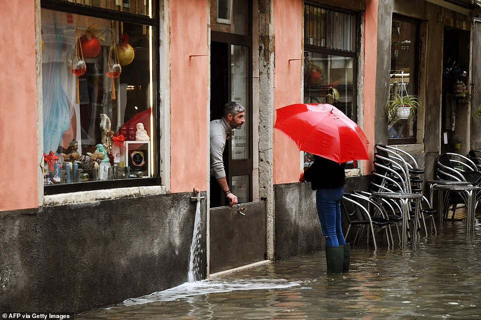 "A shop owner protects water from getting in on December 8, in Venice following a high tide ""Alta Acqua"" event following heavy rains and strong winds"