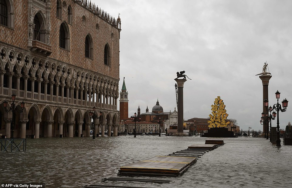 A view shows a flooded St. Mark's Square by the Doge's Palace and a luminous Christmas Tree installation by Italian artist Fabrizio Plessi on Tuesday