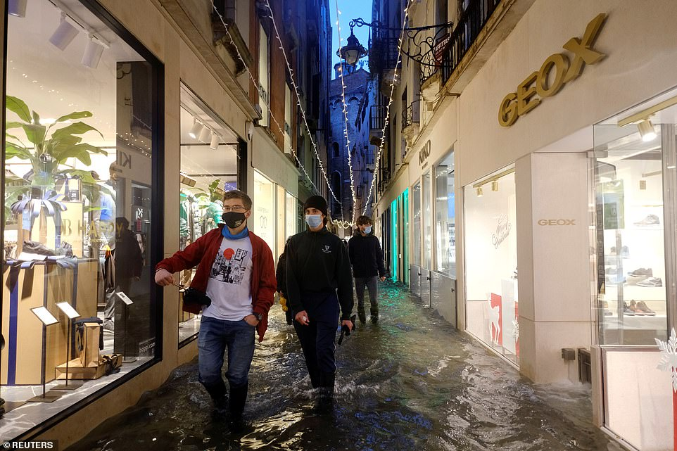 The system of 78 flood gates designed to protect the city from tides of up to 3 metres (10 ft) requires 48-hours notice to be activated. Pictured people walking in a flooded street