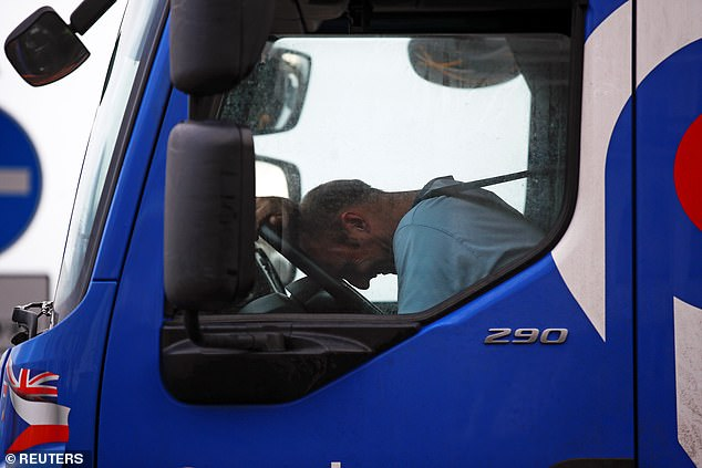 Such is the mounting chaos in UK ports right now that there are fears that Christmas will be ruined for millions of families who won't get the goods and gifts they have ordered in time. Pictured: A lorry driver reacts as he queues to enter the port of Dover