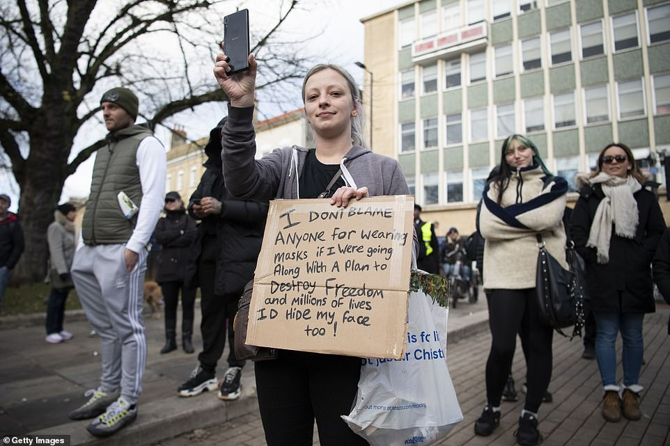 A woman held a sign reading 'I don't blame anyone for wearing masks if I were going along with a plan to destroy freedom and millions of lives I'd hide my face too' during the demonstration in Bristol