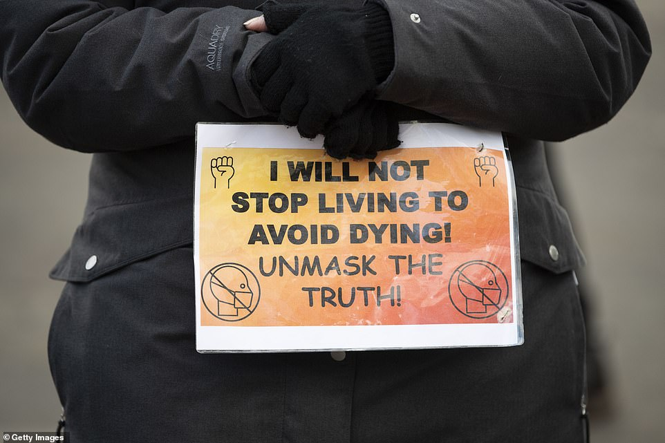 A close-up of a sign that read 'I will not stop living to avoid dying. Unmask the truth' during an anti-vaccine protest which started at College Green in Bristol