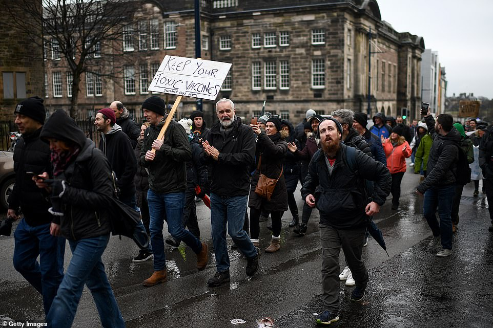 A man walked with a placard reading 'keep your toxic vaccines' as protestors walked in the rain to complain about strict lockdowns and a vaccine they don't trust