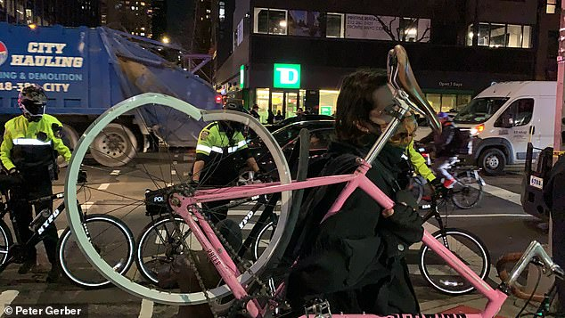 A protester holds up their mangled bicycle after they were struck by the vehicle Friday