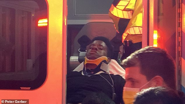 An injured protester is seen being loaded into an ambulance following the incident which left six people in hospital