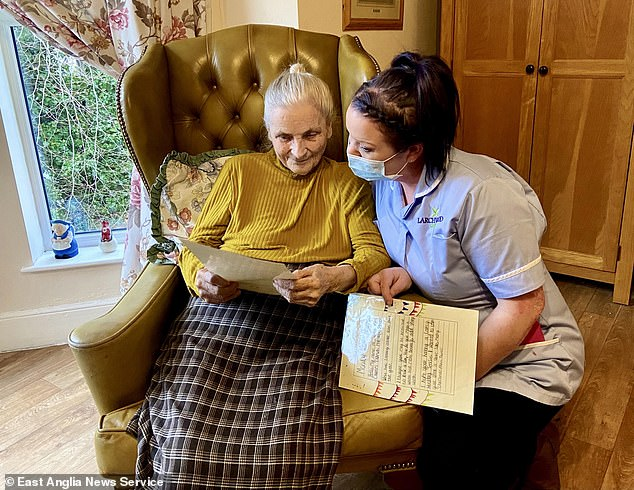 Sybil Bissett, 93, a resident at Hillcrest care home in Norwich, Norfolk, reads a letter from a pupil