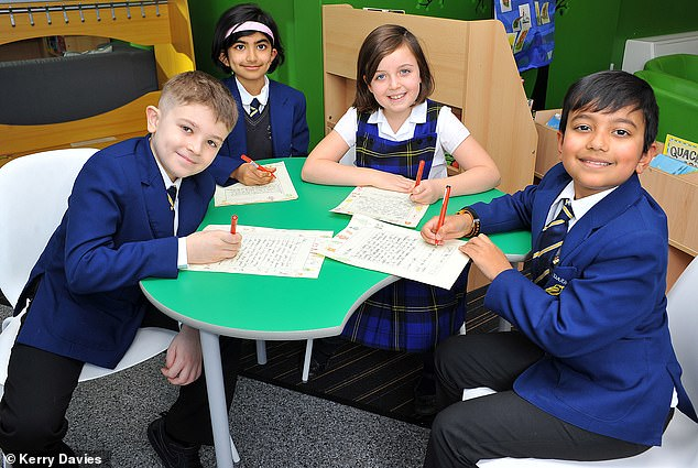 Pupils at Charles Darwin Primary School write letters to send to residents at the care home