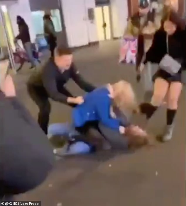 Eventually three people approached the women and attempted to break the fight