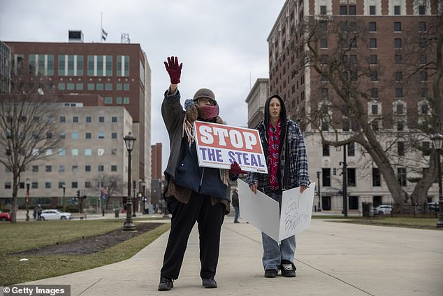 Two pro-Trump demonstrators stand outside the Michigan state capitol on Monday as Electoral College electors make Joe Biden's election win official
