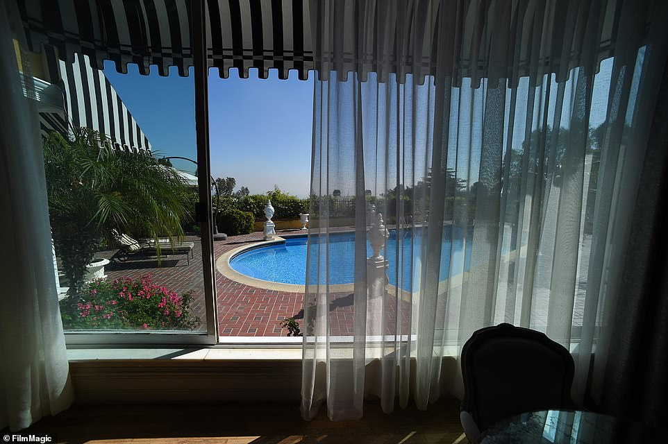 A view of the pool from inside the mansion. Outside the home, there's a brick patio, cabana and two motor courts