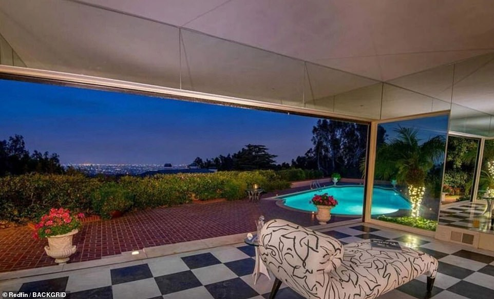 The home sits on a 1.1-acre lot in Bel Air and has spectacular views of the city below. A view of the pool against the evening sky