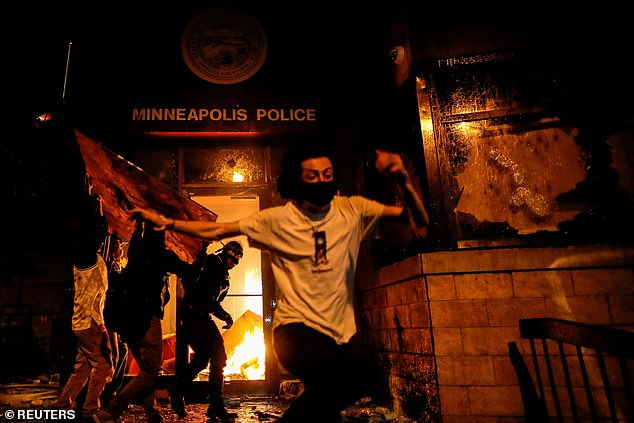 Protesters react as they set fire to the entrance of a police station in Minneapolis on May 28