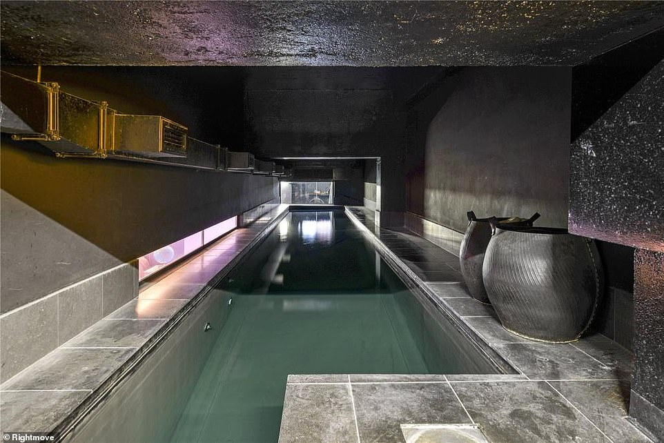 Not a white tile in sight: The swimming pool has grey tiles with black painted ceiling and walls