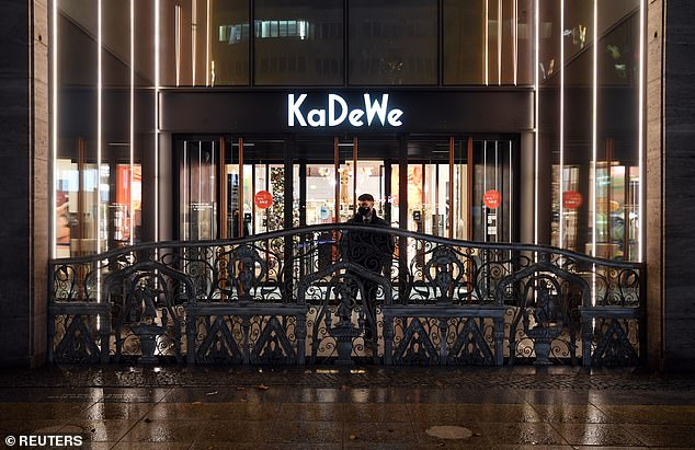 A security guard closes the iron gate at Berlin's famous KaDeWe department store last night as it closes its doors during Germany's second national lockdown