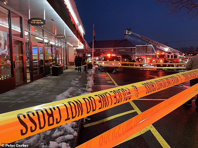 Pictured: Police rope off the area around the Verizon store where the crash happened