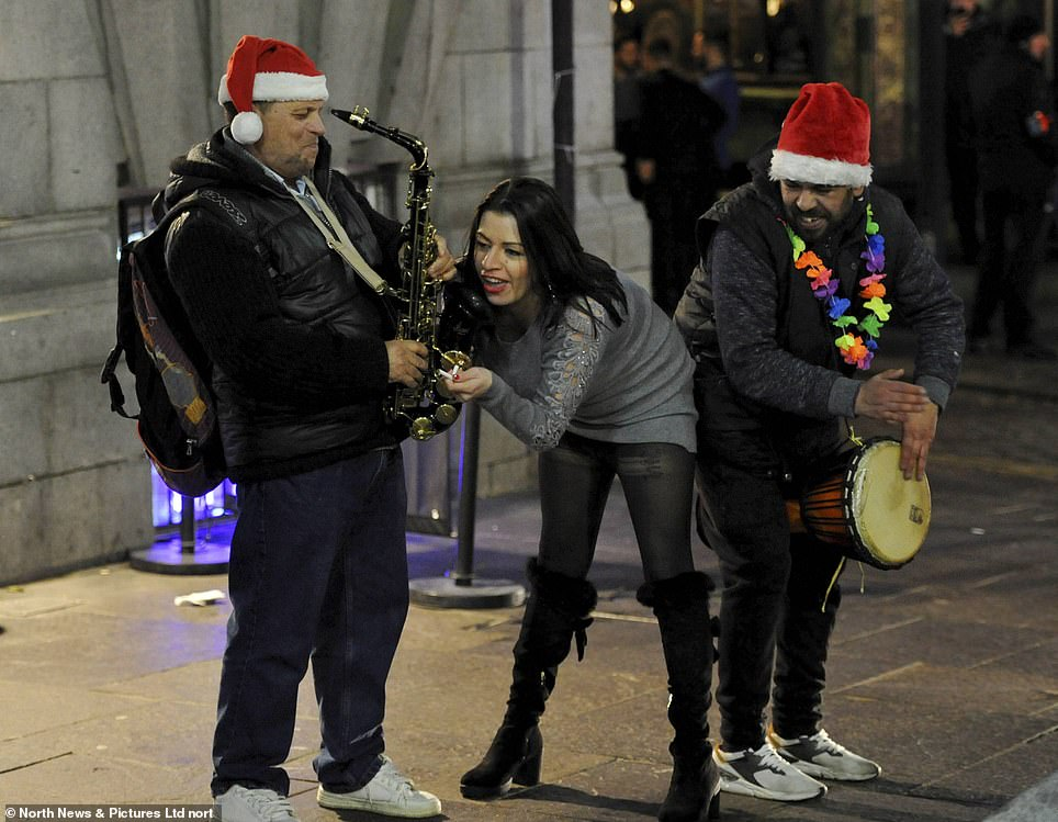 A woman tries to play along with musicians on the streets ofNewcastle in 2019