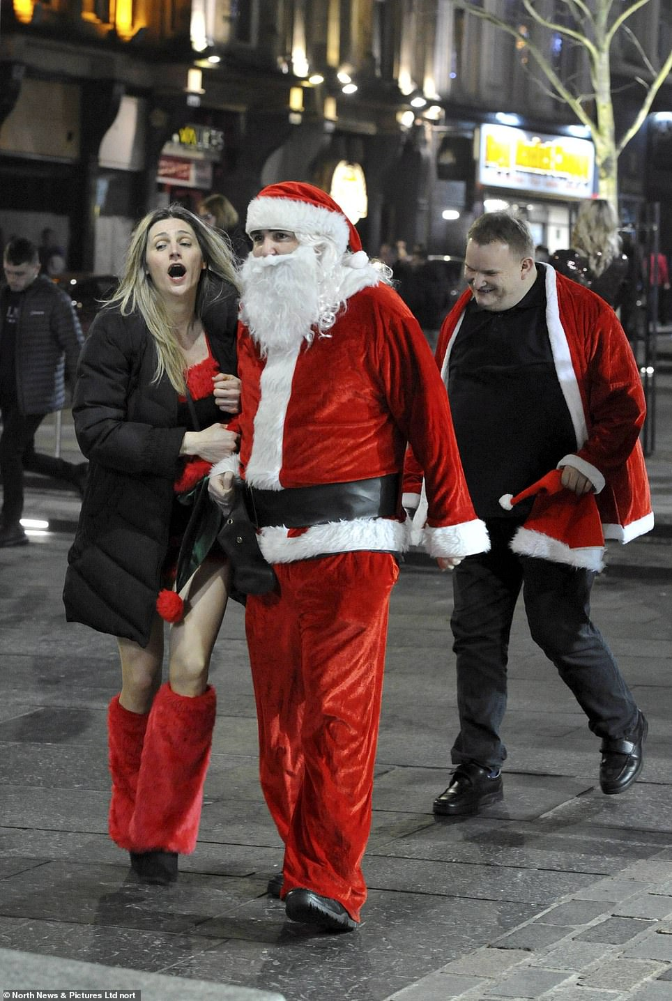 A woman clutches onto a man dressed as Santa as they walk the streets ofNewcastle in 2019