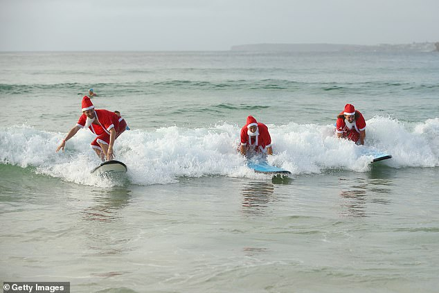 Pictured: surfing Santas on an overcast Bondi Beach. Millions of Sydney residents are in for a crappy Christmas this year thanks to a covid outbreak coupled with a forecast of rain
