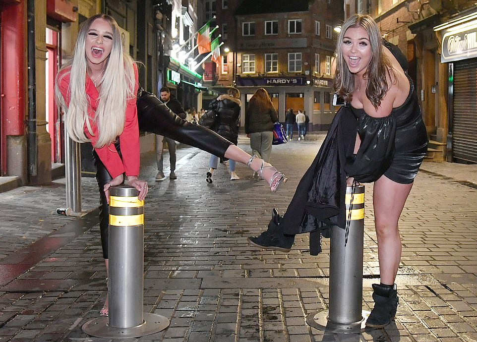 Two revellers remain socially distanced on the streets of Liverpool where Tier 2 rules mean pubs and restaurants are open