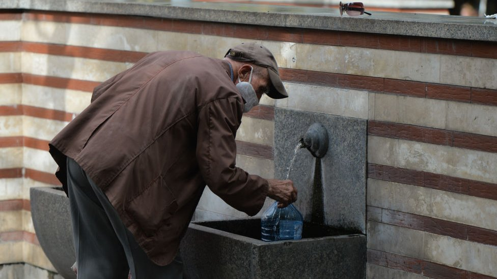 Man drinking water from a fountain in Sofia, Bulgaria.