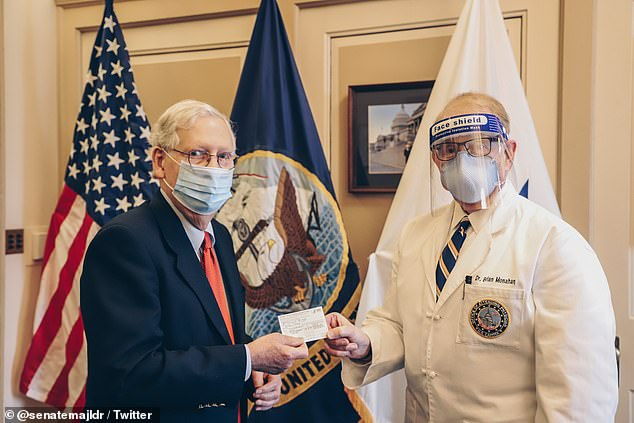 Senate Majority Leader Mitch McConnell (left) tweeted out a photo ofDr. Brian Monahan (right), the Capitol physician, handing the Kentucky Republican his proof of vaccination card