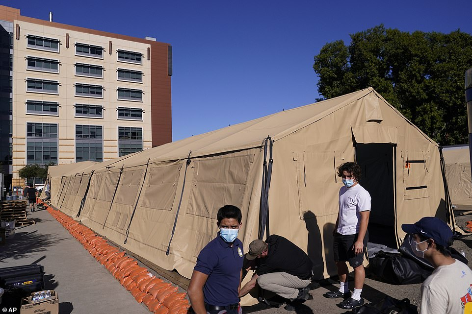 Engineers and volunteers stand outside a mobile field hospital at UCI Medical Center, Monday.The number of people hospitalized across California with confirmed COVID-19 infections is more than double the state's previous peak, reached in July, and a state model forecasts the total could hit 75,000 patients by mid-January