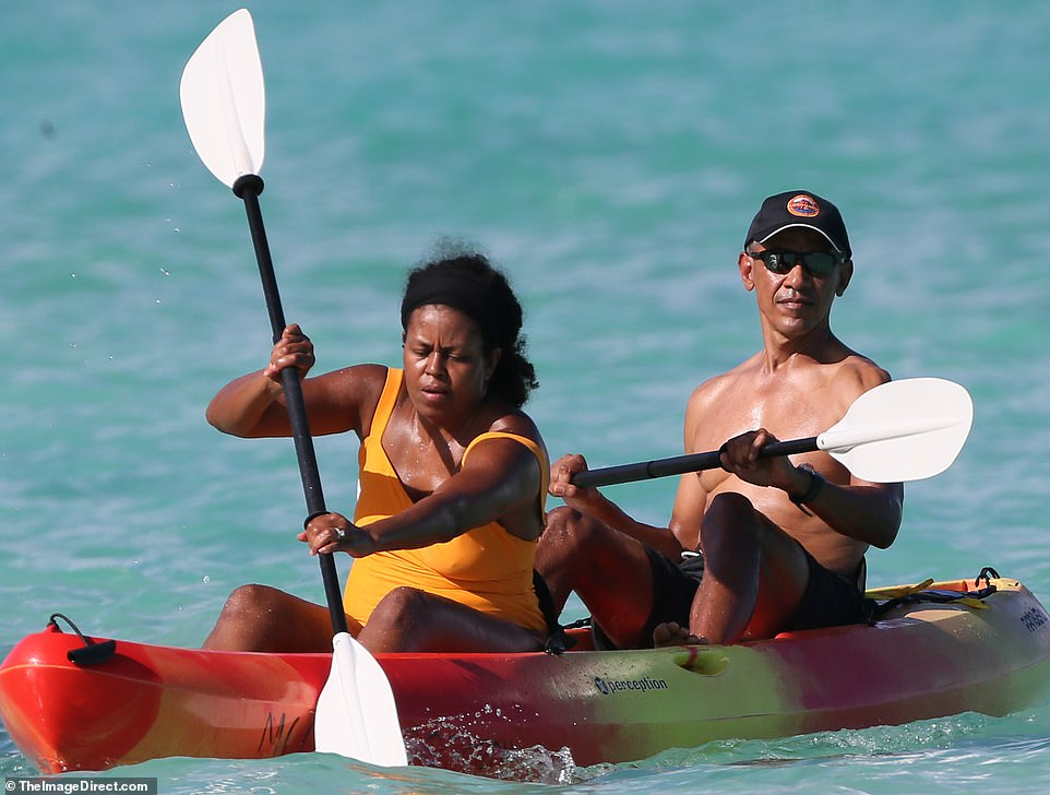 Michelle, wearing a bright orange swimsuit, gets stuck in as Barack takes in the scenery