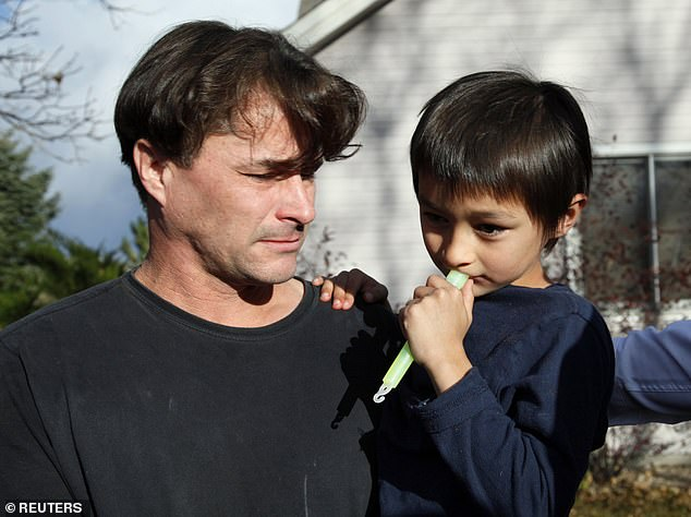 Richard Heene (L) reacts as he holds his son six-year-old Falcon Heene outside their house in Fort Collins, Colorado October 15, 2009