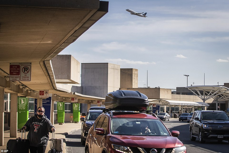 Cars wait for travelers outside a terminal at the Dallas/Fort Worth International Airport on Wednesday, Dec. 23, 2020