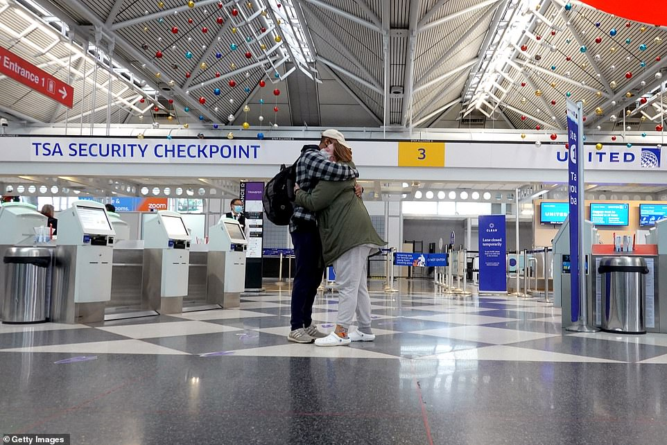 Some travelers were elderly and said they'd figured they didn't have many Christmases left, other said they'd traveled to keep long distance romances alive (Pictured:A traveler says goodbye at O'Hare International Airport on December 23)