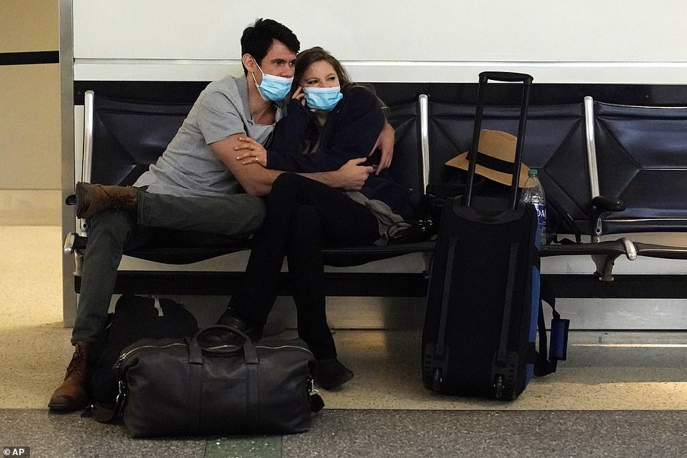 Other travelers said they just yearn for the human connection that's been absent for the past nine months (Pictured: Travelers embrace in terminal at LAX)