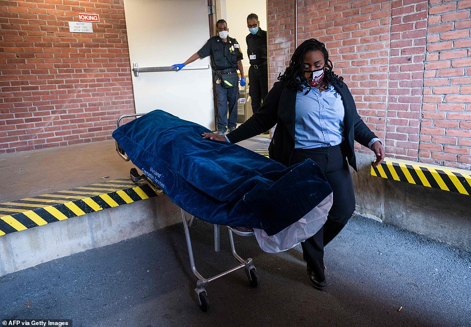 Maryland Cremation Services transporter Morgan Dean-McMillan moves a suspected Covid-19 positive body to her van on Wednesday. There have been 327,853 deaths from the virus nationwide as of Christmas Eve