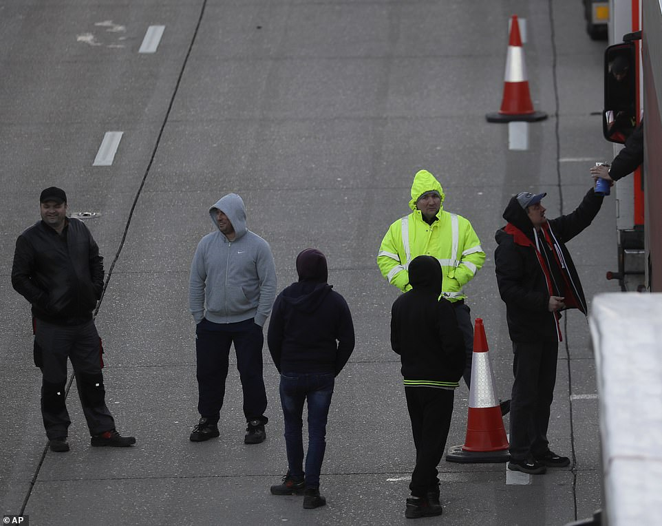 Drivers walk on the motorway on Christmas Day as their trucks are parked up on the M20, with more arriving to join the queue