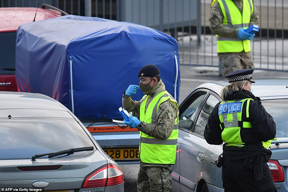 Members of the British army help travellers to use covid-19 self-testing kits close to the entrance to the Port of Dover