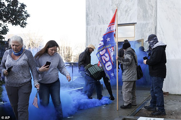 One of those outbreaks resulted in seven deaths while the other recent outbreak has led to more than 300 people placed in quarantine. Pictured,protesters in Oregon opposed to COVID-19 restrictions attempt to force their way in during the a special legislative session