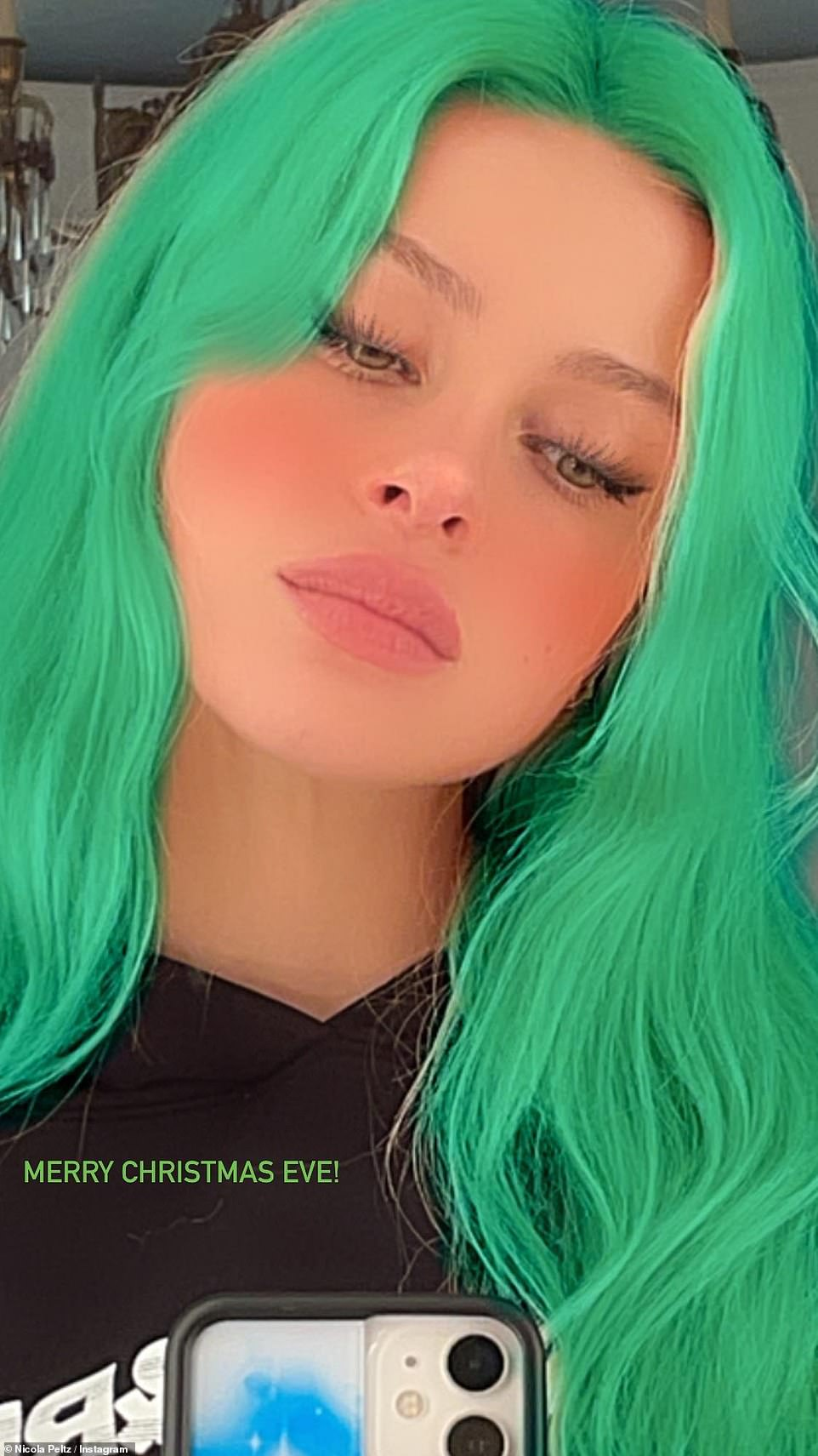 Apart for Christmas: Brooklyn's fiancé Nicola Peltz shared a snap in bright green hair as she celebrated Christmas Eve in the US