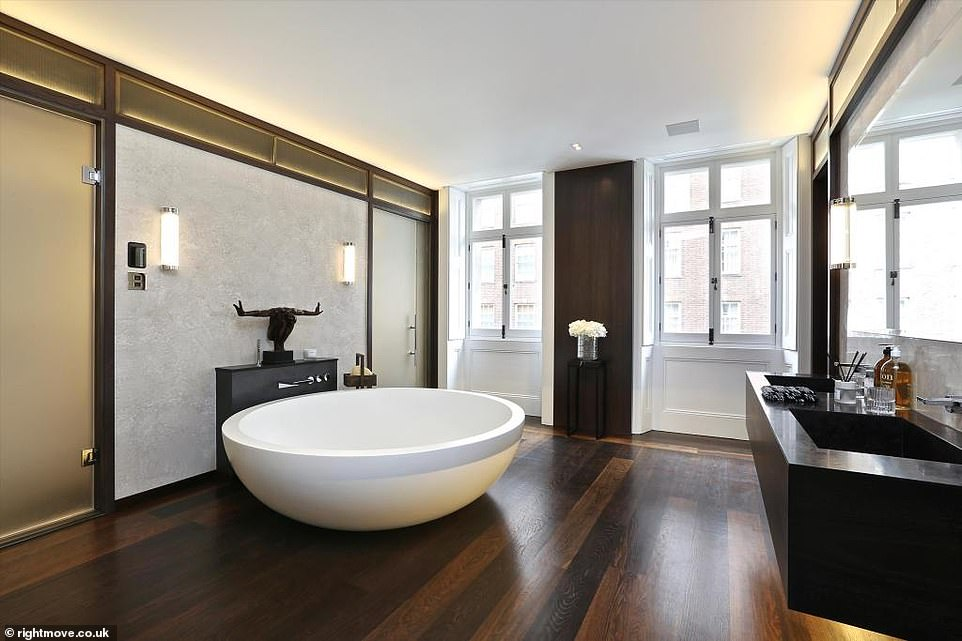 Pictured: One of the property's bathrooms. A large stand-alone bath gives the room a breathtaking centre feature and the wooden floors and wall finishings give it a timeless feel