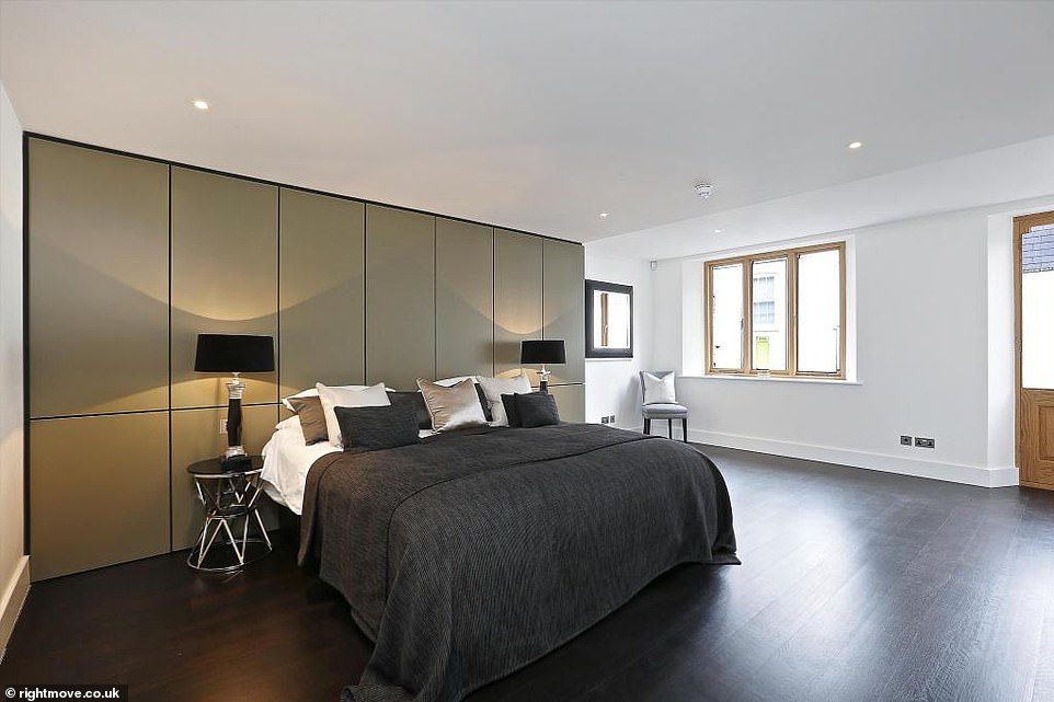 One of the property's 12 bedrooms has a bright, sleek finish with clean wooden floors and panelled walls. The black touches add a classic, strong finish