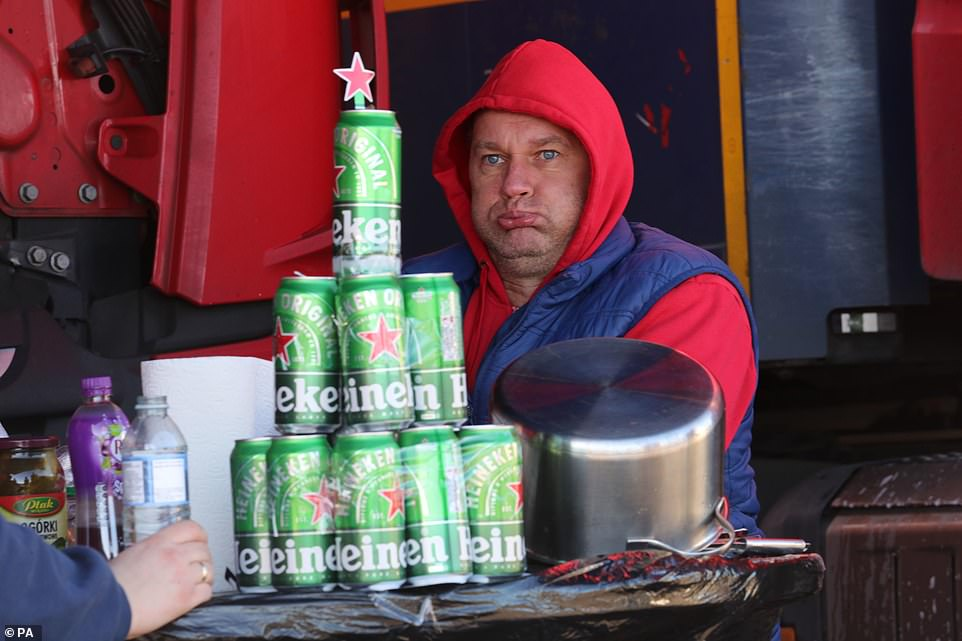 A Polish lorry driver, who has fashioned a makeshift Christmas tree out of empty Heineken cans, waits at a truck stop near Folkestone, Kent